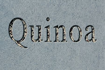 chiseled: Text engraving word quinoa with quinoa grains filling up the engraving Stock Photo