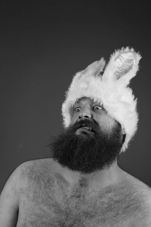 mouthing: Shocked bearded fat man wears silly bunny ears