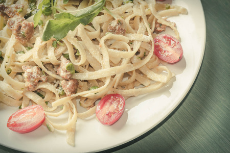 conscious: Italian health conscious fettuccine alfredo with halved cherry tomatoes and arugula garnish Stock Photo