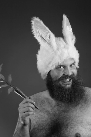 hurtful: Grinning bearded fat man wears silly bunny ears Stock Photo