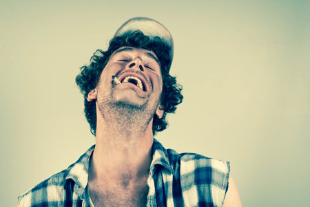 redneck: Laughing redneck burts into hysterics as he smokes his cigarette Stock Photo