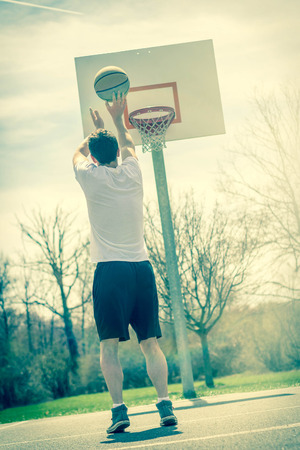 early twenties: Young man shooting free throws from the foul line