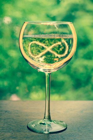 infinity symbol: Glowing glass of white wine for summer celebration or holidays