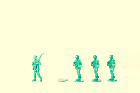 green plastic soldiers: Green army man steps off his foot stand for new adventure Stock Photo