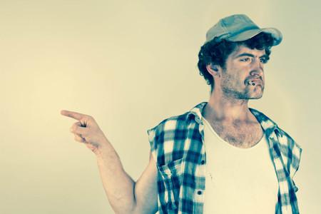 blaming: Blaming redneck bosses everyone around as he smokes his cigarette Stock Photo