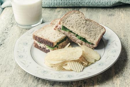 potato tuna: Tuna salad sandwich with ripple potato chips and a glass of milk