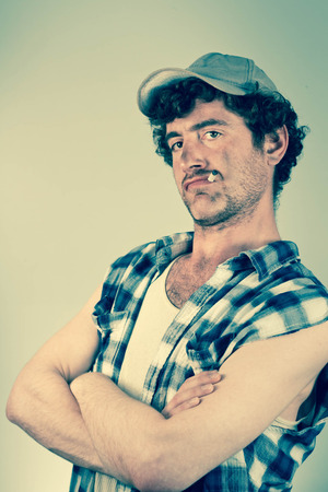redneck: Confident redneck folds his dirty arms while smoking a cigarette Stock Photo