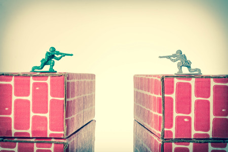 Rival toy army men aim guns at eachother atop opposing toy bricks