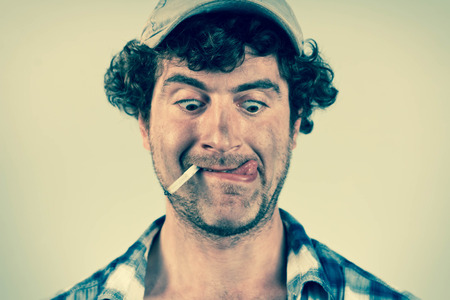 hick: Hungry redneck licks his lips while smoking a cigarette Stock Photo