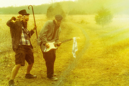 hobo: Stylish gypsies play trumpet and electric guitar on a wilderness path in grainy old fashioned grunge photo