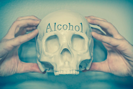 death head holding: Engraved word Alcohol on skull spells out cause of death