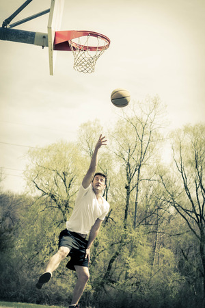 Young man doing basketball trick shots as he leaps through the air