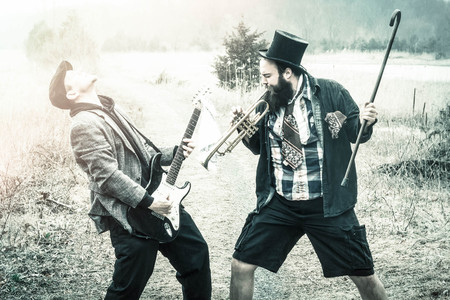 vagabond: Stylish gypsies play trumpet and electric guitar on a wilderness path