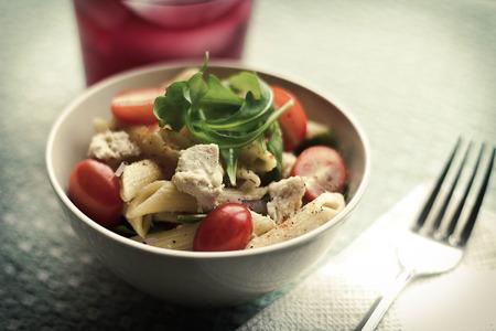 Penne pasta tuna salad with fresh grape tomatoes and arugula