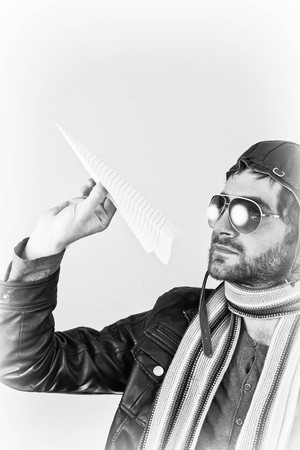 ambivalent: Aviator pilot with hat and sunglasses plays with paper planes