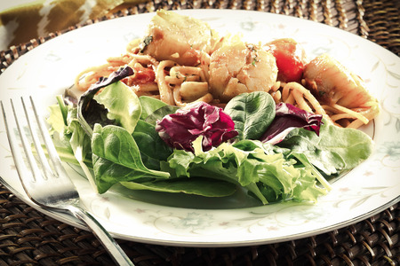 linguine pasta: Fresh scallops with linguine pasta and tomato sauce with a side salad Stock Photo