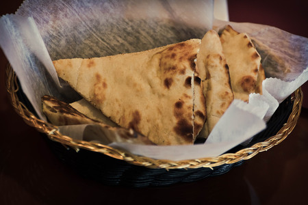 Fresh hot sliced naan bread in decorative basket