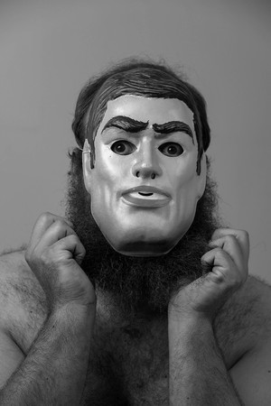 A shirtless bearded man wears a creepy mask