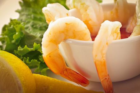 romaine: fresh shrimp cocktail with sauce, lemon wedges, and garnished with crispy romaine lettuce