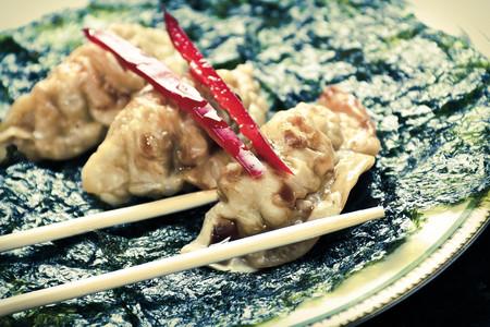 Fried Japanese dumplings on crispy roasted seaweed and red pepper garnish Stock Photo
