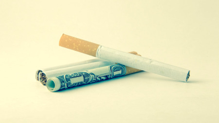 actual: Closeup of cigarettes - one of them is an actual dollar