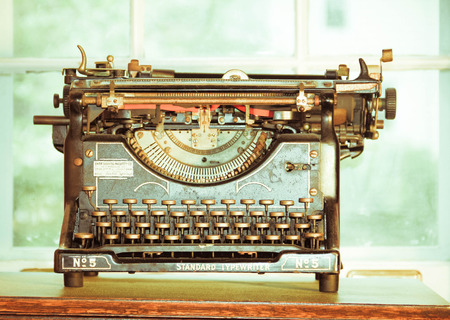 An old vintage typewriter on a desk.