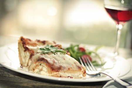 Home made cheese lasagna with arugula salad and a glass of red wine