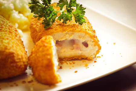cordon: Breaded stuffed chicken cordon bleu with green peas white rice and parsley for garnish