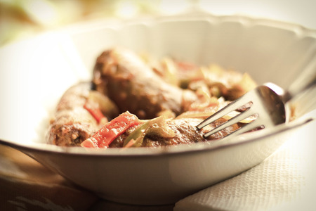 italian sausage: Spicy Italian sausage onion and bell peppers in a bowl Stock Photo