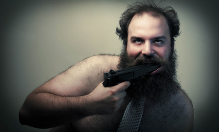 suicidal: A suicidal crazed businessman loses his shirt and holds a gun to his mouth Stock Photo