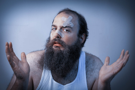 shrugs: A bandaged bearded man shrugs his hands in confusion