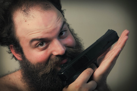 mugging: A balding bearded man mugs for the camera while displaying his pistol