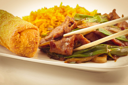 take out: Take out Chinese sauteed fried beef strips with scallion served with an egg roll and pork fried rice Stock Photo