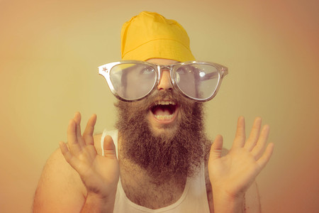 wacky: A wacky excited bearded man puts his hands in the air with a smile