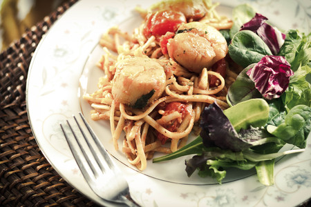 side salad: Fresh scallops with linguine pasta and tomato sauce with a side salad Stock Photo