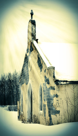 pealing: Sunbeams on an old abandoned snow covered church building Stock Photo