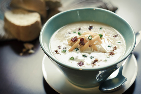 Creamy loaded baked potato soup with scallion garnished and fresh Italian bread Stock Photo