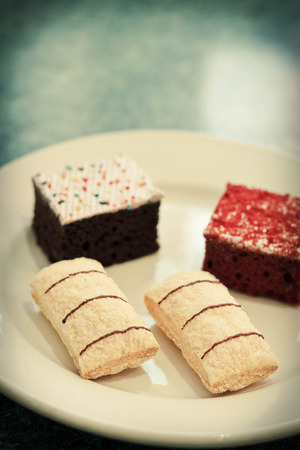 jimmies: Assortment of sweet and colorful dessert cakes on a plate Stock Photo