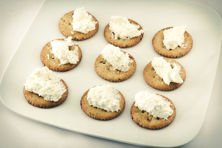 Snack plate of crackers topped with whipped cream cheese