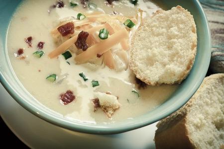 scallion: Creamy loaded baked potato soup with scallion garnished and fresh Italian bread Stock Photo