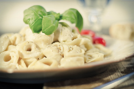 alfredo: Cheese tortellini in a creamy alfredo sauce garnished with fresh basil leaves