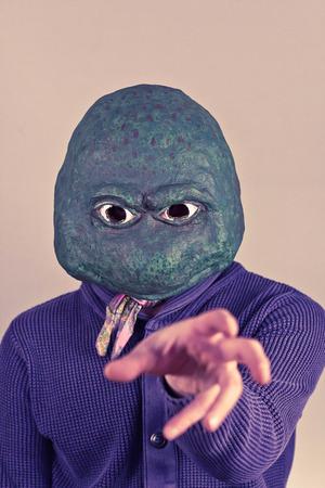 Creepy bald lizard man wearing a blue sweater