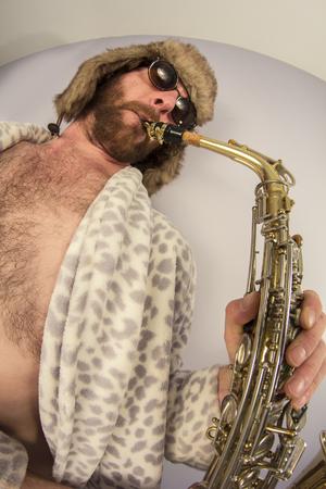 weirdo: Bearded hipster plays jazz saxophone in leopard print bathrobe taken with fisheye lens