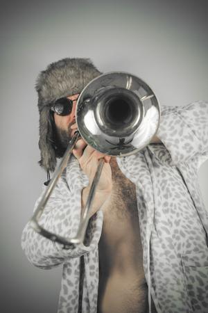 weirdo: Bearded hipster plays jazz trombone in leopard print bathrobe Stock Photo