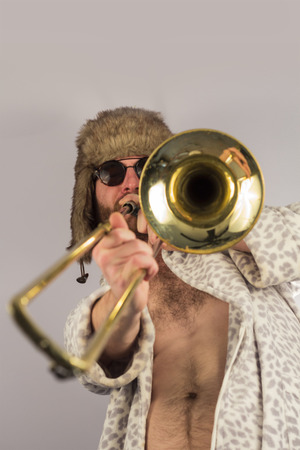 trombone: Bearded hipster plays jazz trombone in leopard print bathrobe Stock Photo