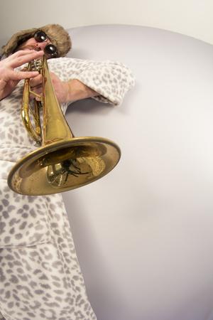 fisheye: Bearded hipster plays jazz trumpet in leopard print bathrobe taken with fisheye lens Stock Photo