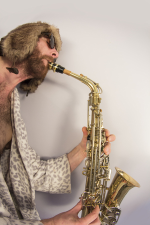 hairy: Bearded hipster plays jazz saxophone in leopard print bathrobe taken with fisheye lens