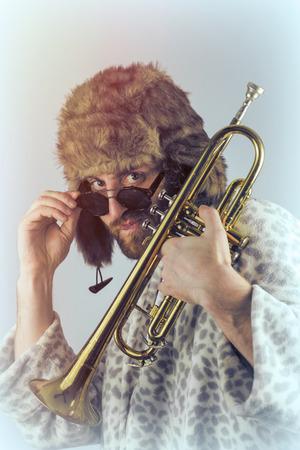 weirdo: Bearded hipster plays jazz trumpet in leopard print bathrobe