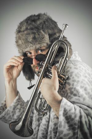 hobo: Bearded hipster plays jazz trumpet in leopard print bathrobe