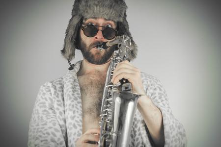 weirdo: Bearded hipster plays jazz saxophone in leopard print bathrobe Stock Photo